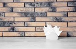 Tenedor de la servilleta con las servilletas de papel en la tabla contra la pared de ladrillo fotografía de archivo libre de regalías