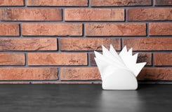 Tenedor de la servilleta con las servilletas de papel en la tabla contra la pared de ladrillo imagenes de archivo