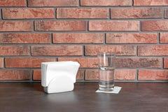 Tenedor de la servilleta con las servilletas de papel y vaso de agua en la tabla fotografía de archivo