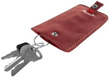 Tenedor dominante de cuero rojo con llaves aislado en el fondo blanco foto de archivo libre de regalías