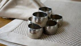 Tenedores de los anillos de servilleta del metal plateado sobre una estera de lugar de oro del color Aliste para el ajuste de la  imágenes de archivo libres de regalías