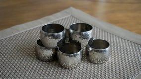 Tenedores de los anillos de servilleta del metal plateado sobre una estera de lugar de oro del color Aliste para el ajuste de la  foto de archivo libre de regalías