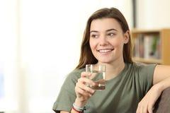 Tenencia adolescente al vidrio de agua que mira el lado en casa Foto de archivo libre de regalías
