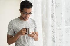 Tenencia adolescente asiática una taza con las bebidas calientes por la mañana Imagenes de archivo