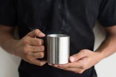 Tenencia adolescente asiática una taza con las bebidas calientes por la mañana Foto de archivo