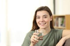 Tenencia adolescente feliz al vidrio de agua que le mira Fotos de archivo libres de regalías