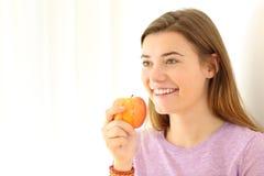 Tenencia adolescente feliz una manzana que mira lejos Foto de archivo libre de regalías