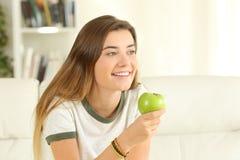 Tenencia adolescente feliz una manzana que mira lejos en casa Fotos de archivo