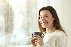 Tenencia adolescente feliz una taza de café que presenta en un día lluvioso Imagenes de archivo