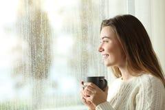 Tenencia adolescente feliz una taza que mira a través de una ventana Imagen de archivo libre de regalías