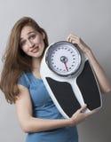 Tenencia adolescente femenina pasmada su escala del peso para comprobar control de peso Foto de archivo libre de regalías