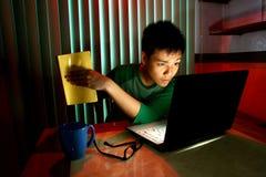 Tenencia adolescente joven un libro delante de un ordenador portátil Fotografía de archivo libre de regalías