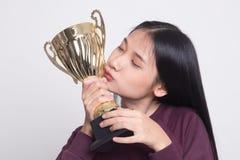 Tenencia asiática joven acertada de la mujer que besa un trofeo foto de archivo