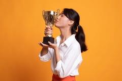 Tenencia asi?tica joven acertada de la mujer que besa un trofeo fotos de archivo libres de regalías