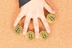 Tenencia Bitcoin de oro de la mano del hombre en fondo texturizado marr?n del corcho fotos de archivo libres de regalías