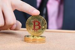 Tenencia Bitcoin de oro de la mano del hombre en fondo texturizado marr?n del corcho imagenes de archivo