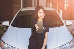Tenencia de la mano de la mujer y móvil con en el fondo del coche, concepto que llama servicio del mecánico del taller de reparac fotografía de archivo