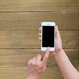 Tenencia de la mano de la mujer y móvil con, teléfono celular Fotos de archivo libres de regalías