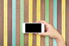 Tenencia de la mano de la mujer y móvil con, teléfono celular, teléfono elegante con la pantalla aislada Foto de archivo