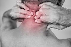 Tenencia de la mano del hombre mayor él cuello y masaje en área del dolor clos foto de archivo