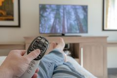 Tenencia de la mano teledirigida para la TV mientras que se relaja con para arriba - la profundidad del campo baja apoyada pies imágenes de archivo libres de regalías