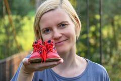 Tenencia de la mujer en zapatos de un bebé rojos del brazo extendido pequeños fotos de archivo libres de regalías