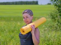 Tenencia de la mujer rodada encima de la estera del ejercicio Foto de archivo libre de regalías