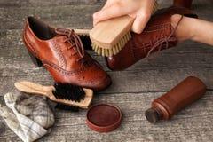 Tenencia del artesano y zapato de la limpieza con el cepillo Imagenes de archivo