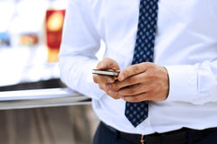 Tenencia del hombre de negocios y usar el teléfono elegante móvil Foto de archivo