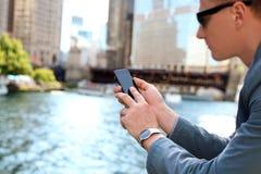 Tenencia del hombre de negocios y usar el teléfono elegante móvil afuera Foto de archivo libre de regalías