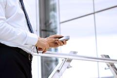Tenencia del hombre de negocios y usar el teléfono elegante móvil en la oficina Imagen de archivo libre de regalías