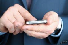 Tenencia del hombre de negocios y usar el teléfono móvil fotografía de archivo libre de regalías