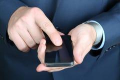 Tenencia del hombre de negocios y usar el teléfono móvil foto de archivo libre de regalías