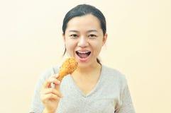 Tenencia feliz joven de la mujer y consumición del pollo de las fritadas Foto de archivo