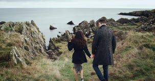 Tenencia hermosa de los pares de las manos que corren hacia el mar Cámaras lentas metrajes