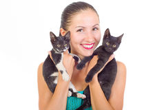 Tenencia sonriente de la muchacha de dos gatitos Foto de archivo libre de regalías