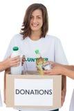 Tenencia voluntaria sonriente una caja de la donación de la comida Foto de archivo