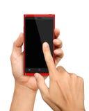Tenencia y tacto de la mano en Smartphone rojo Fotografía de archivo