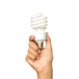 Tenendo e alzi una lampadina a spirale disponibila Fotografia Stock