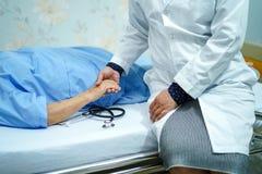 Tenendo il paziente senior delle mani commoventi o anziano asiatico della donna della signora anziana con amore, la cura, aiutant fotografie stock