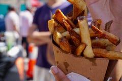 Tenendo le patate fritte per andare in un cono di carta eliminare trasportatore, all'aperto immagini stock libere da diritti