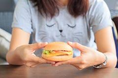 Tenendo nella donna passa l'hamburger degli alimenti a rapida preparazione, l'hamburger degli alimenti a rapida preparazione del  Immagini Stock
