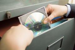 Tenendo un archivio del CD in gabinetto Immagine Stock Libera da Diritti