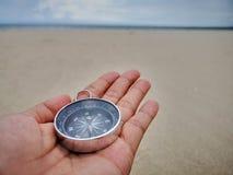 Tenendo una bussola che mostra il punto di direzione al Nord e ad affrontare l'oceano fotografia stock