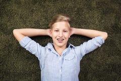 Tener el adolescente de la diversión miente en una alfombra Imagenes de archivo