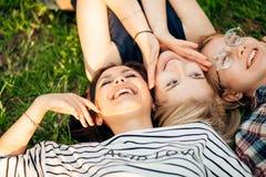 Tener mejor tiempo con los amigos grupo de estudiantes que mienten en el goce de la hierba Foto de archivo