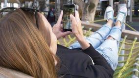 Tener resto en la hamaca de la ciudad, selfie de la toma de la mujer de piernas almacen de metraje de vídeo