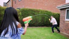 Tener una lucha del agua con el papá en el jardín almacen de metraje de vídeo