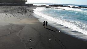 Άνδρας και ένα ερωτευμένο ζεύγος γυναικών που αγκαλιάζει και που περπατά κατά μήκος της ακτής του νησιού στον Ατλαντικό Ωκεανό Ζε φιλμ μικρού μήκους
