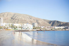 Tenerife beach with ferry and a kid. Sunny summer day on Tenerife island Royalty Free Stock Photos